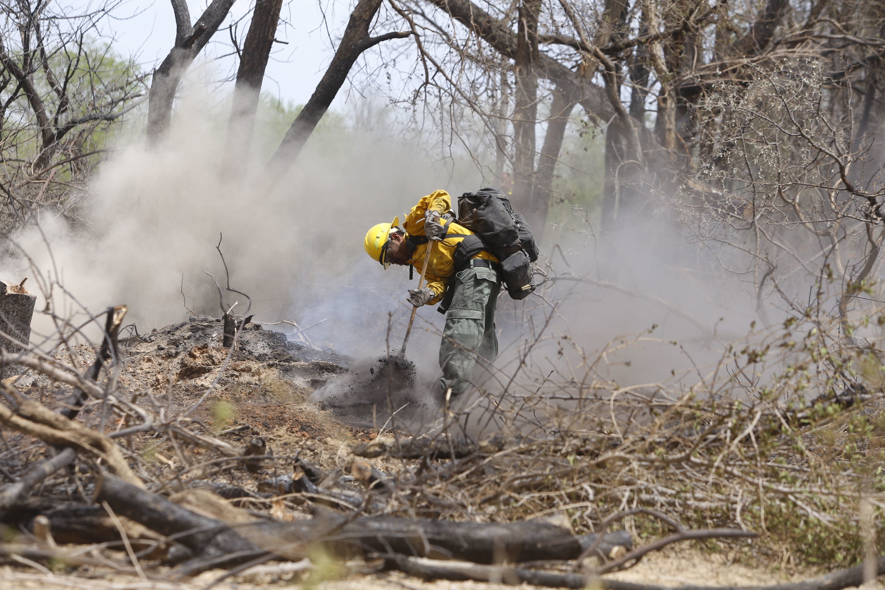 A firefighter works on smoldering tree stumps on April 30, 2018 after a fire burned more than 200 acres near Navajo Route 364 and Fifth Lane in Shiprock.