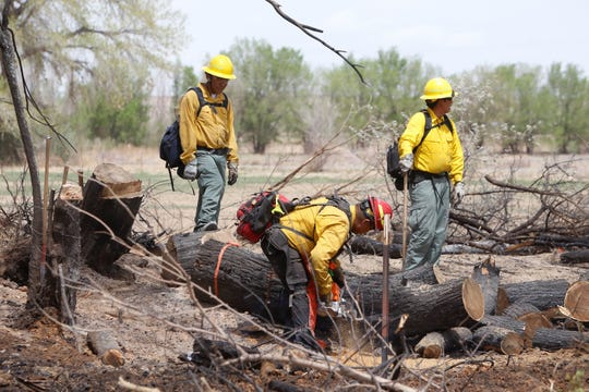 Firefighters from the Bureau of Indian Affairs Navajo Region Wildland Fire Management and the McKinley County Fire Department mop up blazes on April 30, 2018 after a fire burned more than 200 acres near Navajo Route 364 and Fifth Lane in Shiprock.