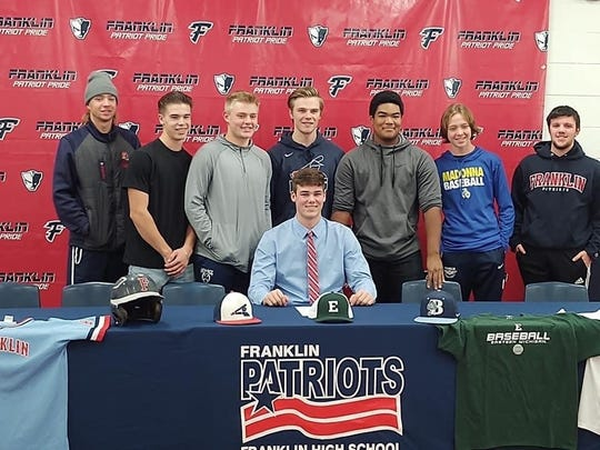 Livonia Franklin pitcher Alex Forry signed with Eastern Michigan as his teammates stood behind him.