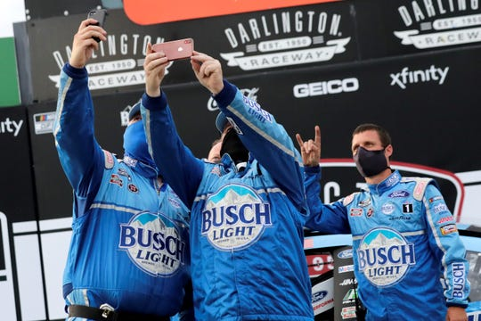 Members of Kevin Harvick's team, all wearing masks, celebrate after winning the NASCAR Cup Series auto race Sunday, May 17, 2020, in Darlington, S.C. (AP Photo/Brynn Anderson)