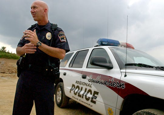 In this file photo from July 15, 2003, former Southwestern Regional Police Officer Stu Harrison is pictured standing in front of a police vehicle.