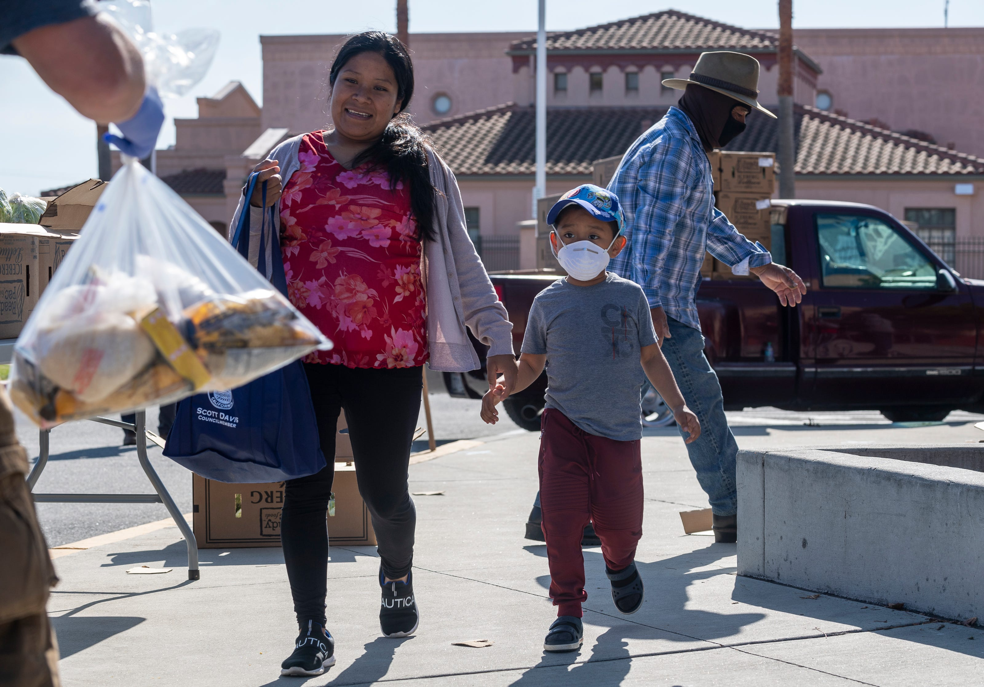 As mother and her son who's wearing a face mask is handed a bag filled with pasta, rice and other essentials during the League of United Latin American Citizens Salinas Council #2055 and United Farm Workers Foundation Food Distribution in Salinas, Calif., on  May 1.