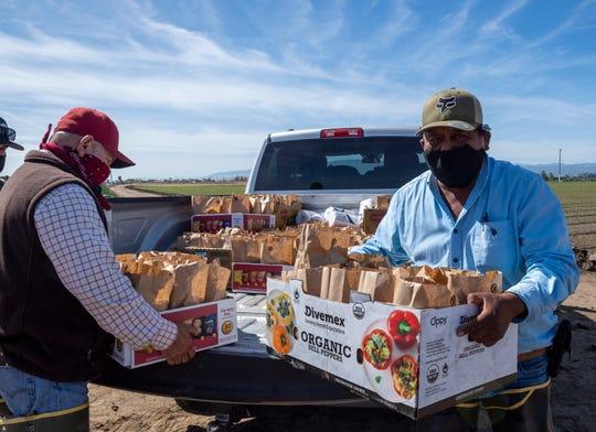 Miguel Alcalá, a la izquierda, y su colega Emilio Velasco llevan cajas llenas de almuerzos donados por los propietarios de negocios locales para distribuirlos a los trabajadores agrícolas en Salinas, Calif., el 16 de mayo. Cada bolsa de comida contiene un sándwich de carne deshebrada, papas fritas y agua embotellada.