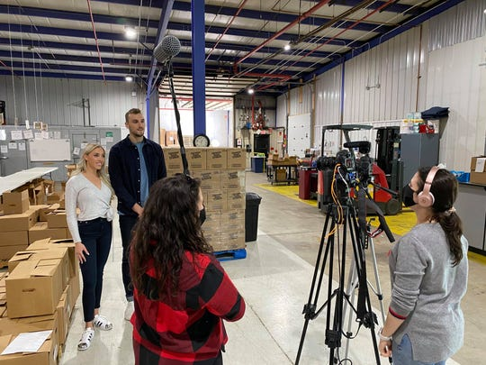 Olivia Harlan Dekker and Sam Dekker stand before a camera to film a PSA for the Sheboygan County Food Bank.