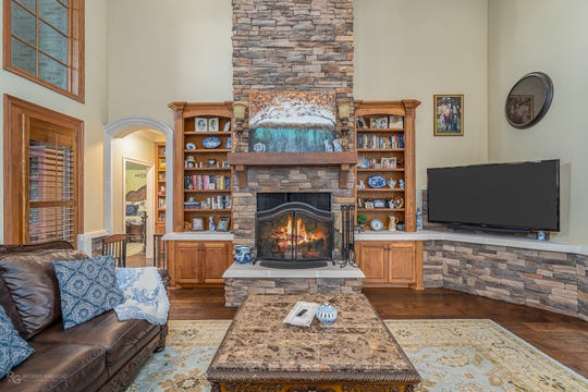 The living space boasts a massive stacked stone fireplace.