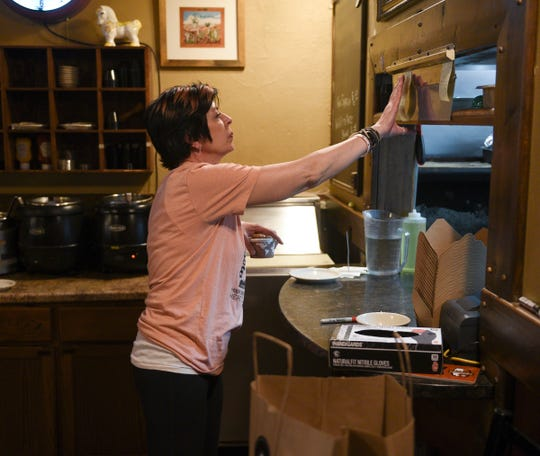 White Horse owner Jackie Lee fills an order Tuesday, May 19, 2020, in St. Cloud.