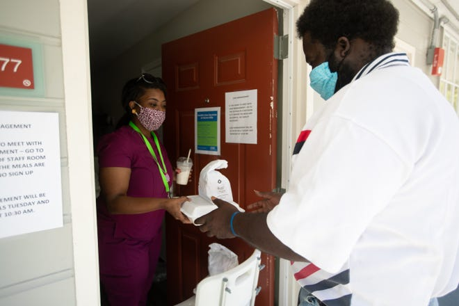 James Banks receives his daily meals from a Kearney Center staff member at one of the shelter's non-congregate locations Tuesday, May 19, 2020.