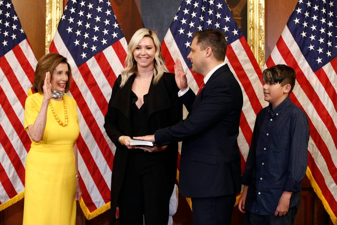 House Speaker Nancy Pelosi of Calif., left, conducts a ceremonial swearing-in for Rep. Mike Garcia, R-Calif., second from right, joined by his wife Rebecca and son Preston, on Capitol Hill in Washington, Tuesday, May 19, 2020.