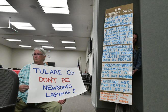Protesters calling for local businesses to reopen hold up signs in the Tulare County boardroom on Tuesday, May 12.