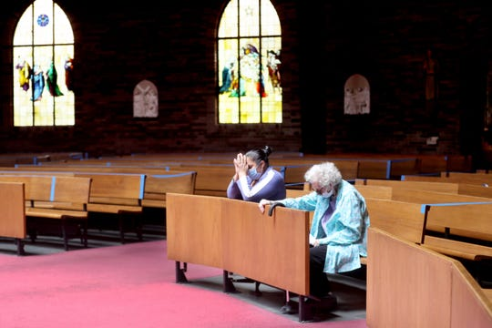 Margaret Mahoney, right, and her aide Maria Villa, pray inside the Transfiguration Church in Tarrytown, N.Y. May 19, 2020. In anticipation of being able to hold services inside the church sanctuary once the coronavirus quarantine is lifted, Fr. Emiel Abalahin, pastor of the church, has taped off sections of the pews so that social distancing among parishioners can be maintained.