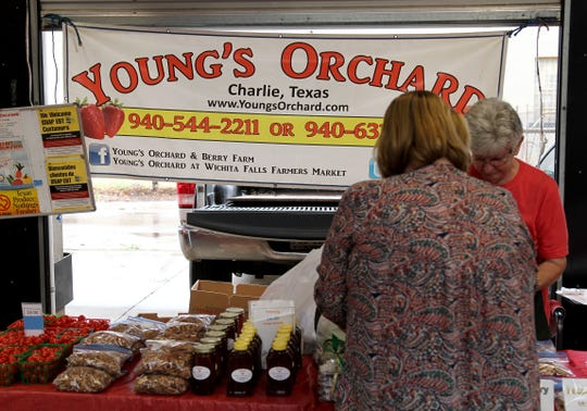 A woman buys produce from Young's Orchard Saturday, May 16, 2020, at the Downtown Farmers Market.