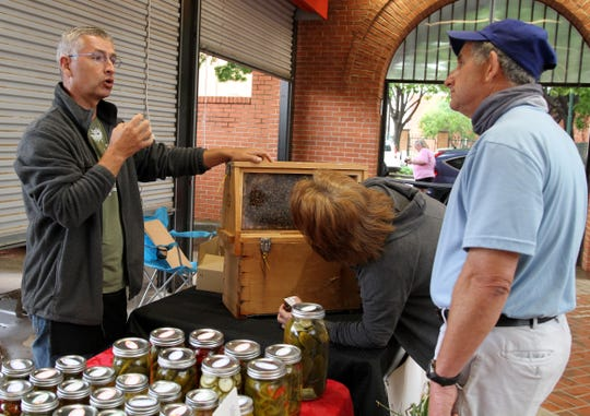 Randy Young talks to shoppers about the bees and local honey sold from Bees' Aria Saturday, May 16, 2020, at the Downtown Farmers Market.