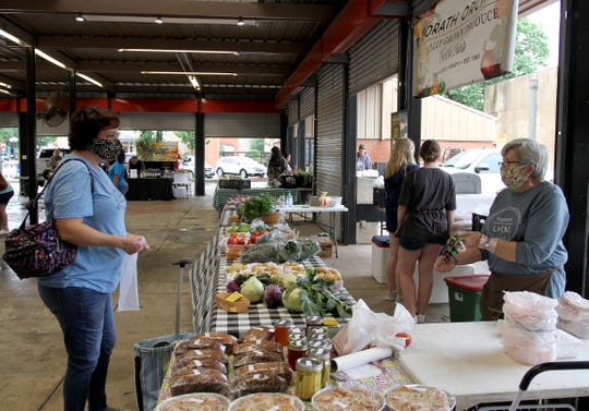 Shoppers and farmers alike wear masks Saturday, May 16, 2020, at the Downtown Farmers Market.