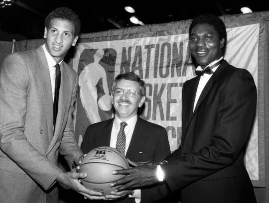 In this June 19, 1984, file photo, NBA Commissioner David Stern, center, is flanked by Akeem Olajuwon, right, the No. 1 pick overall by the Houston Rockets, and Sam Bowie, the No. 2 pick overall by the Portland Trail Blazers at the NBA Draft in New York.
