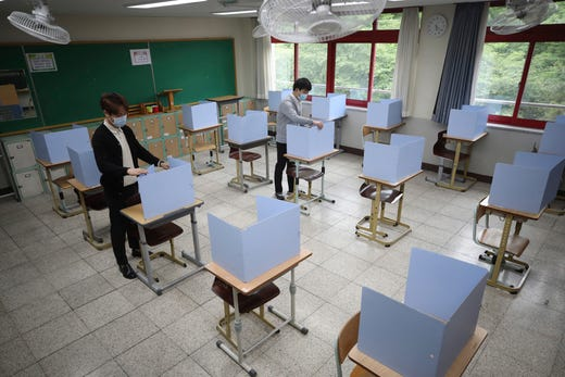Teachers check dividers on desks in a class ahead of school reopening at Junghwa Girls High School in Daegu, South Korea, May 19, 2020. South Korean Vice Health Minister Kim Gang-lip urged vigilance to maintain hard-won gains against the virus and called for education officials to double check preventive measures with high-school seniors returning to school on Wednesday.