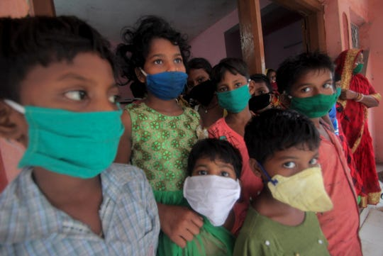Evacuated children wearing masks as a precaution against the spread of coronavirus stand at a relief camp at Paradeep, on the Bay of Bengal coast in Orissa, India, Tuesday, May 19, 2020. Cyclone Amphan was moving toward India and Bangladesh on Tuesday as authorities tried to evacuate millions of people while maintaining social distancing.
