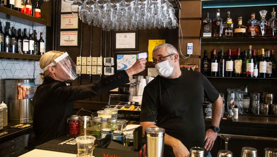 1920 Tavern Owner Jenna Aronowitz takes the temperature of bartender Shane Goode before the Roswell restaurant opens for sit down meals in Brookhaven, Ga., Monday, April 27, 2020.