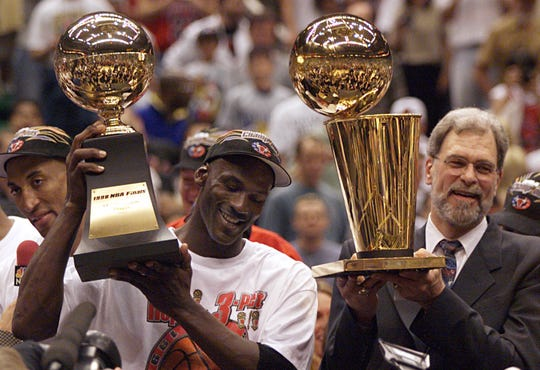 Michael Jordan holds the MVP trophy and coach Phil Jackson holds the championship trophy after the Bulls beat the Jazz to win their sixth title in 1998.