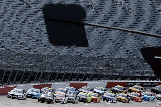 Cars approach the starting line in front of empty grandstands to start Sunday's NASCAR Cup Series race at Darlington Raceway.