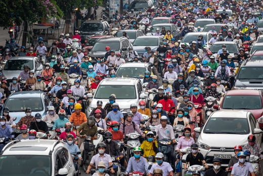 Motorbike riders with face masks are stuck in traffic during the morning peak hour on May 19, 2020 in Hanoi, Vietnam. Though some restrictions remain in place, Vietnam has lifted the ban on certain entertainment facilities and non-essential businesses, including pubs, cinemas and spas & other tourist attractions to recover domestic tourism.