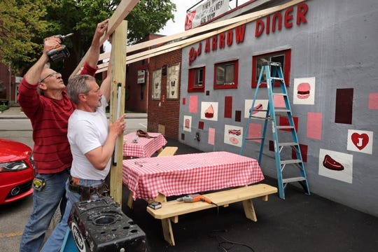Carpenters Tom Percoco, left, and Dan Mercier build an outdoor dining area at the Red Arrow Diner in Manchester, N.H., on May 18, 2020. The diner, which closed their inside dining area in March due to business restrictions created by the COVID-19 virus outbreak, expected to open their outdoor area for customers later in the day Restaurants across New Hampshire reopened to outdoor table service on Monday.