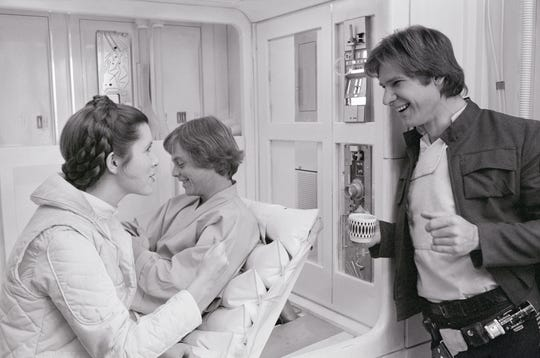Hamil (from behind) smiles when Carrie Fisher and Harrison Ford talk in the infirmary about Hot, where the infamous Luke / Leah kiss took place.