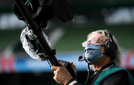 A TV camera operator is seen with a face covering before the Bundesliga match between SV Werder Bremen and Bayer 04 Leverkusen at Wohninvest Weserstadion on May 18, 2020 in Bremen, Germany. The Bundesliga and Second Bundesliga is the first professional league to resume the season after the nationwide lockdown due to the ongoing Coronavirus (COVID-19) pandemic. All matches until the end of the season will be played behind closed doors.