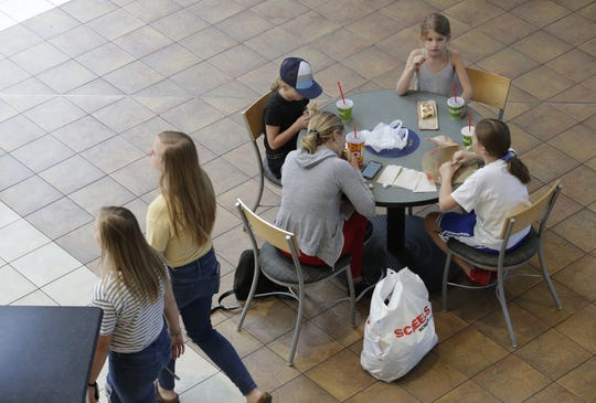 The Baker family of Fond du Lac enjoys lunch as shoppers enter the food court area Wednesday at the Fox River Mall in Grand Chute.
