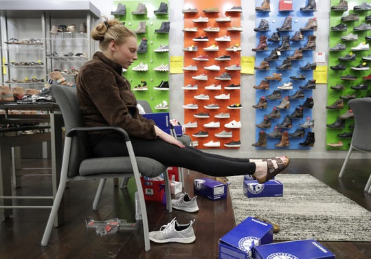 Casey Wulk of Green Bay tries on a pair of sandals at Tradehome Shoes Wednesday at the Fox River Mall in Grand Chute.