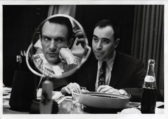 "Richard ""Dick"" Rosenzweig, right, with Hugh Hefner, in mirror, in June 1966."
