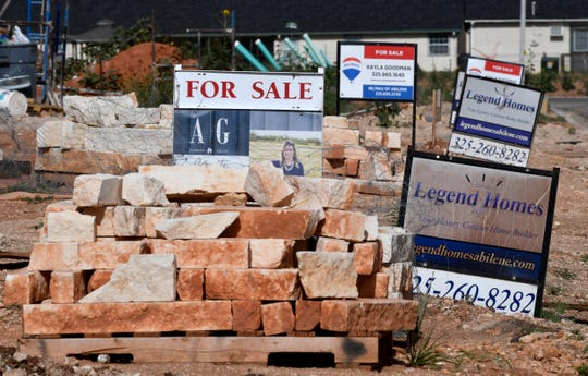 For sale signs are lined up outside homes under construction in the southeastern side of Abilene near Wylie East Elementary School on May 19.