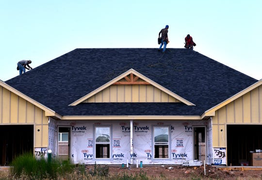Roofers works on a home in a subdivision near Wylie East Elementary School in Abilene on May 19.