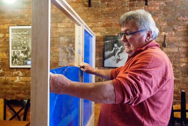 Michel Baudouin, owner of downtown Asheville's Bouchon, peels plastic from a plexiglass divider May 20, 2020.