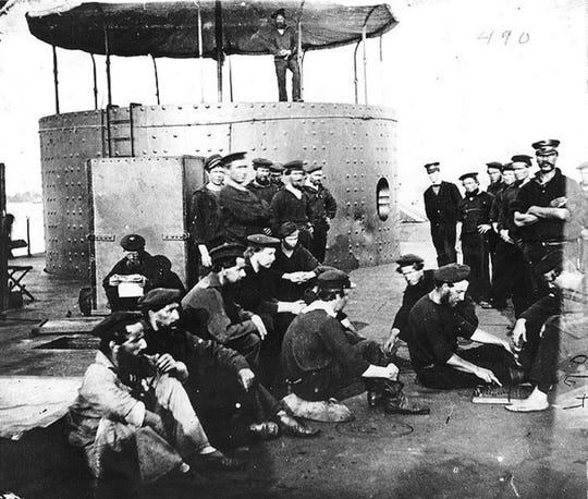 The crew of the USS Monitor sitting next to the revolving turret.