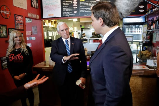 Vice President Mike Pence, center, gestures as he speaks to Florida Gov. Ron DeSantis, right, after ordering lunch at Beth's Burger Bar, Wednesday, May 20, 2020, in Orlando, Fla. Pence was scheduled to participate in a roundtable discussion with hospitality and tourism industry leaders to discuss their plans for re-opening during the coronavirus outbreak. (AP Photo/Chris O'Meara)