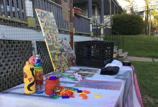 By remote control: An unmanned yard sale displays artwork, magazines and t-shirts on Maple Street in Burlington on May 18, 2020. A sign at the other end of the table notifies customers to pay electronically, using the Venmo app. Gov. Phil Scott announced on May 18 that yard sales in the state could operate during this stage of the coronavirus pandemic — but must limit crowd size