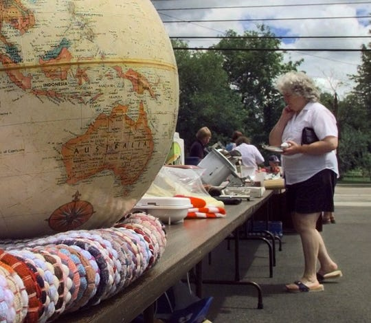 Think globally, pre-pandemic: Shoppers hunt for bargains at a yard sale in Milton to benefit  the Champlain Valley Agency on Aging Senior Meals on Wheels program on July 28, 2000.