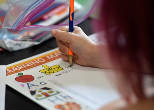 Four-year-old Keeley Mahan writes her name, Wednesday, May 20, 2020, in Portland. Her mom, Jennifer, teaches her during the COVID-19 pandemic.