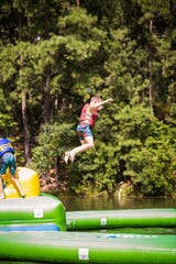 A camper jumps in the water at JCC Camps at Medford. Many area summer camps are on hold due to the pandemic.