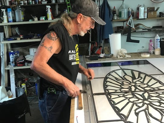 Bernie Evans, Owner of Bernie and Max stained glass studio and supply, works on a project in his workshop under the store on May 19, 2020.