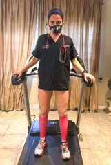 Rachel Belmont in her nursing scrubs at the end of her 100-mile run