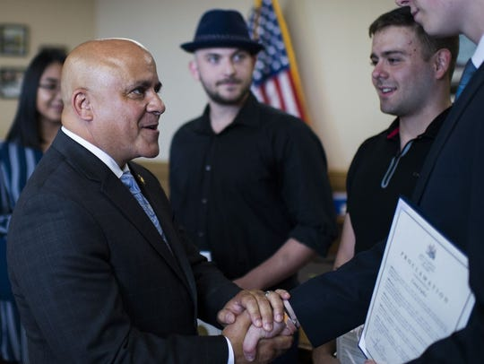 """Jonathan Perez-Gaytan, right, receiving a proclamation from Camden Mayor Francisco """"Frank' Moran in June 2018 for saving a 90-year-old man from a house fire."""