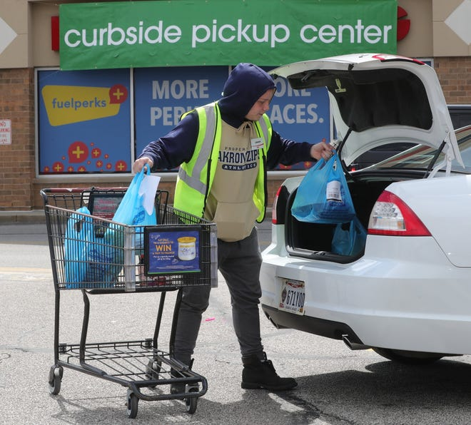 Giant Eagle employee Jensen Barkman loads bags of groceries into the trunk of a car on Howe Ave..