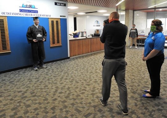 Daniel Burnett has his photo taken by math teacher Paul Bailey of the Coshocton County Career Center while math teacher Melinda Gale watches. Seniors received their Career Passports and had pictures taken to provide closure and recognize their hard work toward graduation.