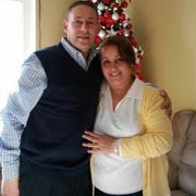 The late Nada Naisan (right) and her husbandNameer Ayram, of Sterling Heights, stand in front of a Christmas tree in 2015. The parents of three children were Iraqi Chaldean refugees who died from the coronavirus. Naisan died on April 21, 2020, and Ayram died 3 weeks later on May 11.