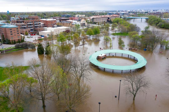 Water floods the Midland Area Farmers Market and the bridge along the Tittabawassee River in Midland, Mich. on Tuesday, May 19, 2020.