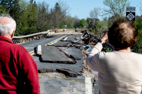 A pair of Midland County residents walk up to one of two bridges on North M-30 that have suffered heavy damage on Wednesday, May 20, 2020 in Edenville Township north of Midland. After two days of heavy rain, the Edenville Dam failed and flood waters rushed south, ravaging the landscape in its path. (Jake May/The Flint Journal, MLive.com via AP)