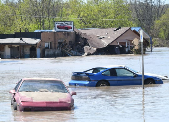 Pontiac Fieros are submerged outside Fieros Forever, a business on the flooded out main street in the Village of Sanford after floodwaters swept through the town.