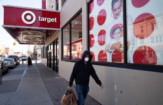 In this April 6, 2020 file photo, a customer wearing a mask carries his purchases as he leaves a Target store during the coronavirus pandemic, in the Brooklyn borough of New York.
