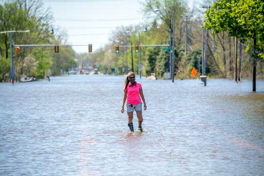 Cyndie Roberts, a math teacher at Dow High School, walks down a flooded North Saginaw Road in Midland trying to get a look at her school, May 20, 2020.